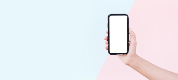 파스텔 핑크와 블루 색상의 표면에 모형과 스마트 폰을 들고 여성 손 클로즈업