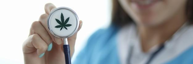 大麻の兆候と聴診器を持っている女性の手のクローズアップ