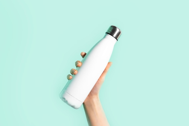 女性の手のクローズアップ、白い再利用可能な鋼のステンレスエコサーモウォーターボトルを持って、シアンの壁に分離された、アクアメンテカラー。プラスチックを使用しないでください。ゼロウェイスト。