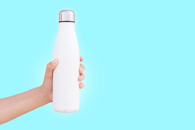 コピースペースでシアン色の表面に分離された白い再利用可能なスチールサーモウォーターボトルを持っている女性の手のクローズアップ。
