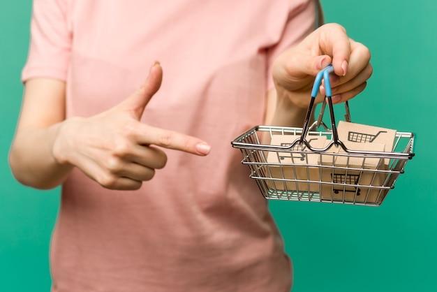 닫기 여성 손 수평 보유 파란색 플라스틱 손잡이와 장난감 금속 쇼핑 바구니