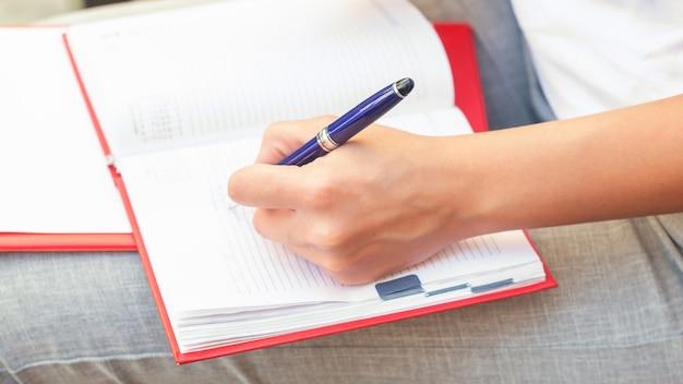 Крупным планом женская рука пишет планы в ноутбук на открытом воздухе