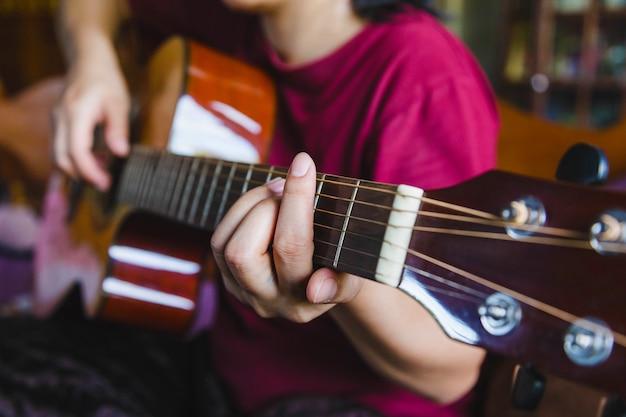ギターを弾く女性の手のクローズアップ。