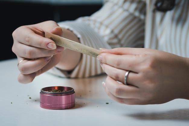 의료 마리화나와 관절을 압 연하는 여성 손 클로즈업.