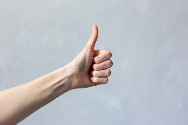 Крупный план женской руки показывает большой палец вверх, на белой поверхности.