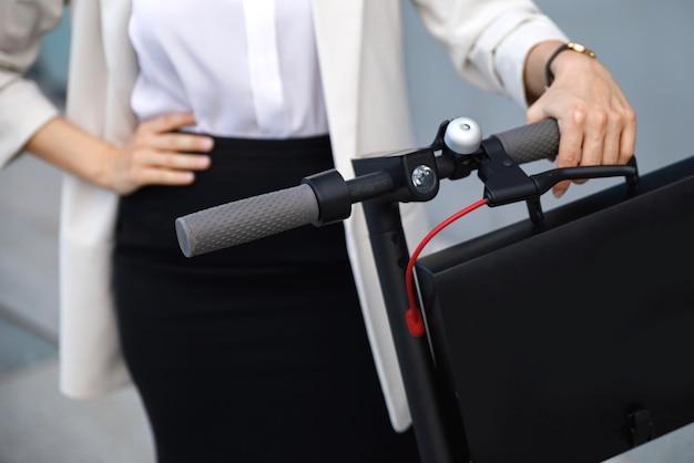 女性の手のクローズアップと電動スクーターのハンドル