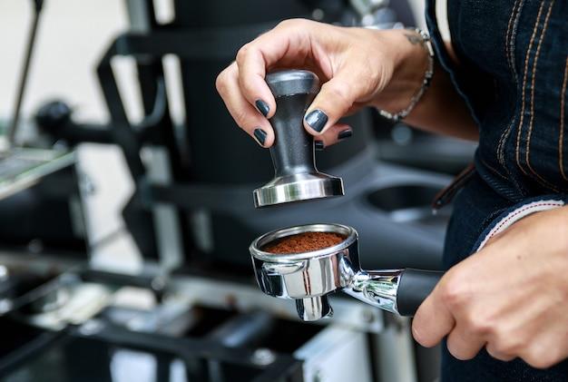 여성 손 클로즈업. 바리 스타가 커피를 만들고 있습니다.
