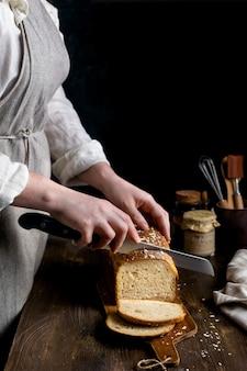 Крупным планом женские руки, режущие домашний цельнозерновой хлеб на закваске