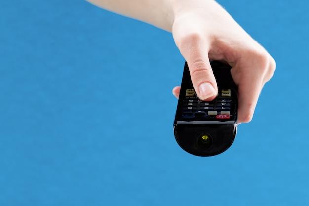 파란색 배경에 tv 채널을 전환하기 위해 검은색 리모컨을 들고 있는 여성의 손을 닫습니다.