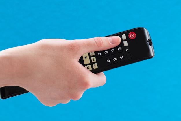 テレビのチャンネルを切り替えるために黒いリモコンを持っている女性の手のクローズアップ