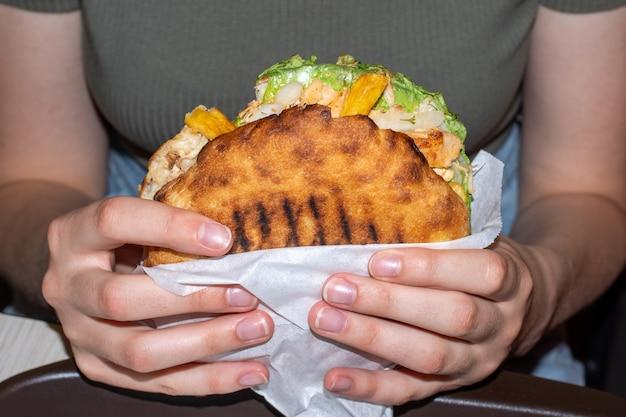 큰 햄버거를 들고 여성 손의 클로즈업, 전면 보기. 건강에 해로운 음식 개념입니다. 과체중 개념입니다.