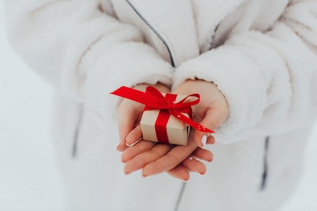 赤いリボンで包まれた小さな贈り物を持っている女性の手のクローズアップ。バレンタイン・デー。