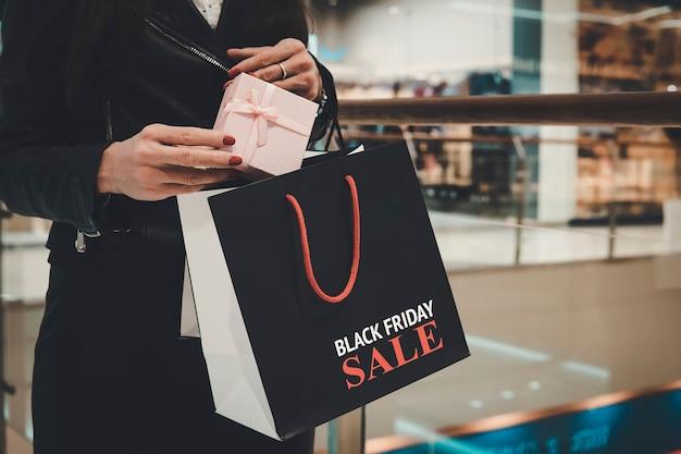 아름다운 상자와 쇼핑백을 들고 있는 여성의 손을 닫고 블랙 프라이데이 세일이라는 문구가 인쇄되어 있습니다. 레이디는 구매 후 선물을 검은색 패키지에 넣습니다. 할인 물건 구매의 개념입니다.