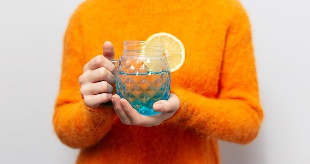 白い背景の上のジュースとレモンの部分と青いガラスのカップを保持している女性の手のクローズアップ。オレンジ色のセーターを着ています。