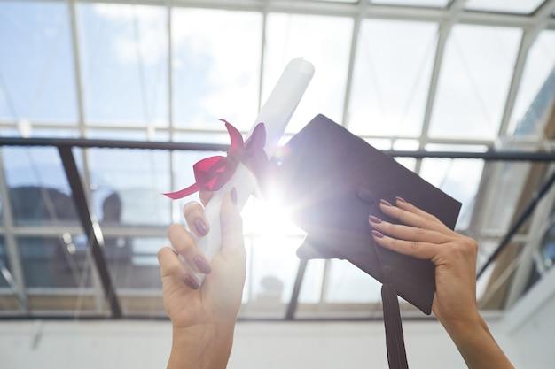 졸업 모자와 졸업장을 햇빛에 들고 있는 여성 손 클로즈업, 공간 복사