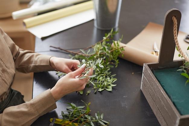 装飾、コピースペースのための花の組成物を作成しながら緑の植物を保持している女性の手のクローズアップ