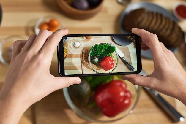 휴대 전화를 들고 그릇에 신선한 야채 사진을 만드는 여성 손의 근접