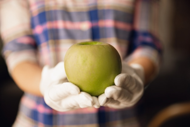 Закройте женские руки в перчатках, держа зеленое яблоко, здоровую пищу, фрукты. диетическое органическое питание, натуральные и свежие продукты, богатые витаминами. готовится, делает предложение кому-то. copyspace.