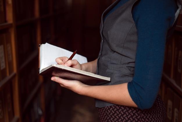 ノートにメモを作っている女性の手のクローズアップ