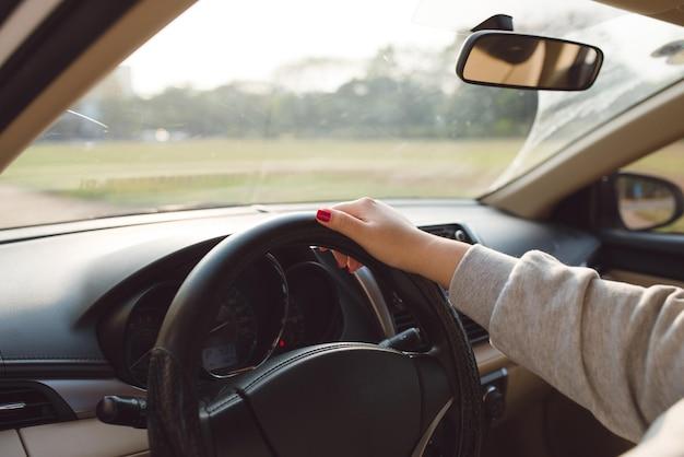 스티어링에 여성의 손을 닫습니다. 자동차 여행에 여행자 소녀, 도 보고. 어깨 너머로 보기