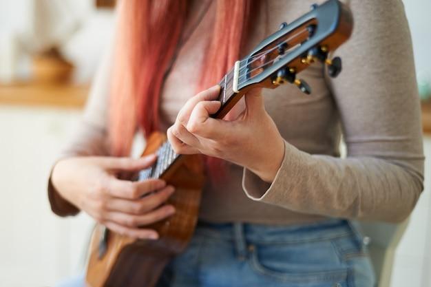 Крупный план женских рук, играющих на гавайской гитаре. выборочный фокус.