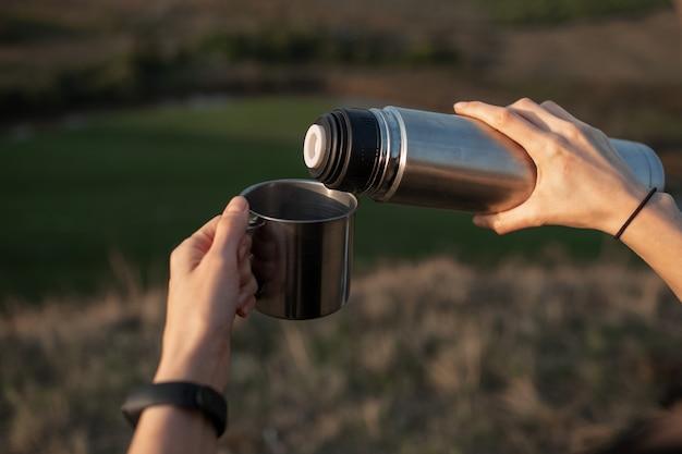 屋外の背景に、魔法瓶からスチールカップに熱いお茶を注いで、女性の手のクローズアップ。旅行とキャンプのコンセプト。
