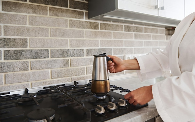 間欠泉のコーヒーメーカーを電気ストーブに置いておいしい香りのよいコーヒーを作る女性の手のクローズアップ。朝のルーチン、朝食の概念