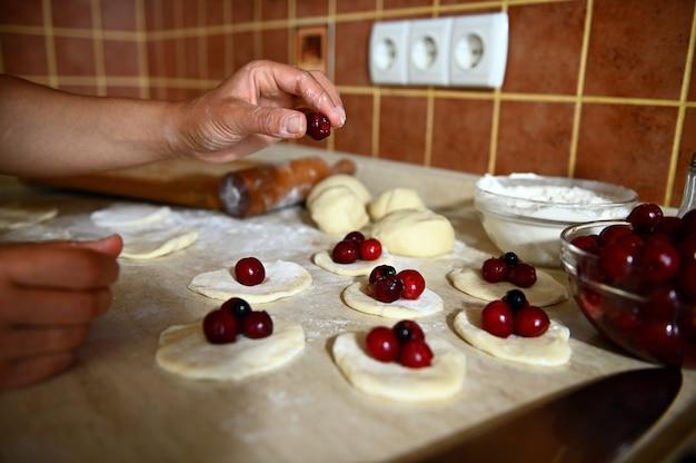 ウクライナの伝統的な餃子を埋める、丸い形の生地にチェリーベリーを置く女性の手のクローズアップ。キッチンで餃子を段階的に調理するプロセス