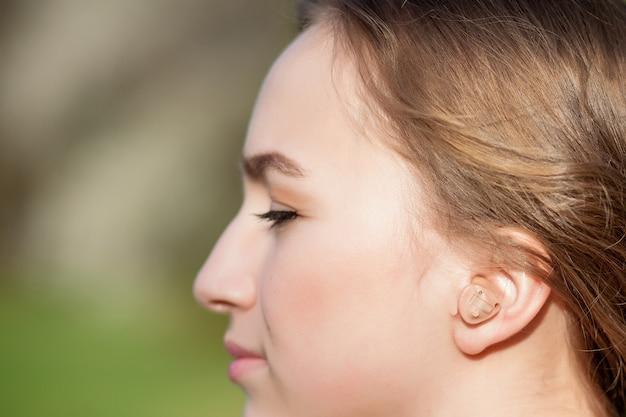 補聴器を耳に入れて女性の手のクローズアップ。