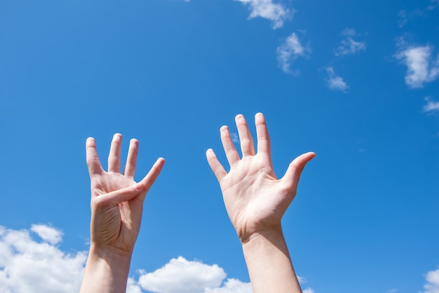Крупный план женских рук, показывающих девять пальцев на фоне голубого неба. номер девять на языке жестов. скопируйте пространство.