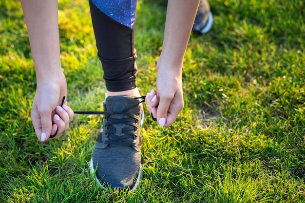 練習前にランニングシューズに靴ひもを結ぶ女性の手のクローズアップ。トレーニングの準備をしているランナー。スポーツアクティブなライフスタイルコンセプト。