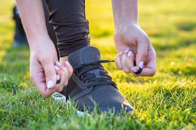 練習前にランニングシューズに靴ひもを結ぶ女性の手のクローズアップ。トレーニングの準備をしているランナー。スポーツのアクティブなライフスタイルのコンセプト。