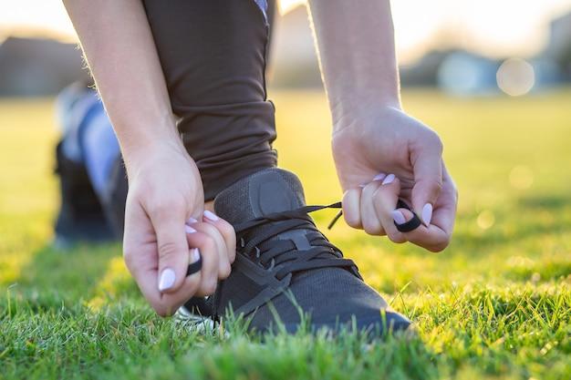 練習前にランニングシューズに靴ひもを結ぶ女性の手のクローズアップ。トレーニングの準備をしているランナー。スポーツアクティブライフスタイル。