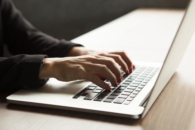 Крупный план женщин руки, набрав на ноутбуке за столом