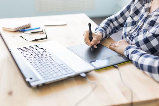 현대 사무실에서 디지털 그래픽 태블릿과 스타일러스를 사용하는 여성 손의 근접