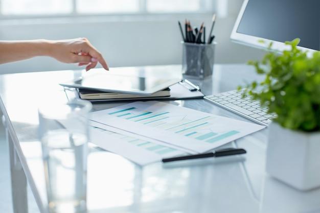 近代的なオフィスのインテリアでコンピューターに取り組んでいる間ラップトップを使用して女性の手のクローズアップ