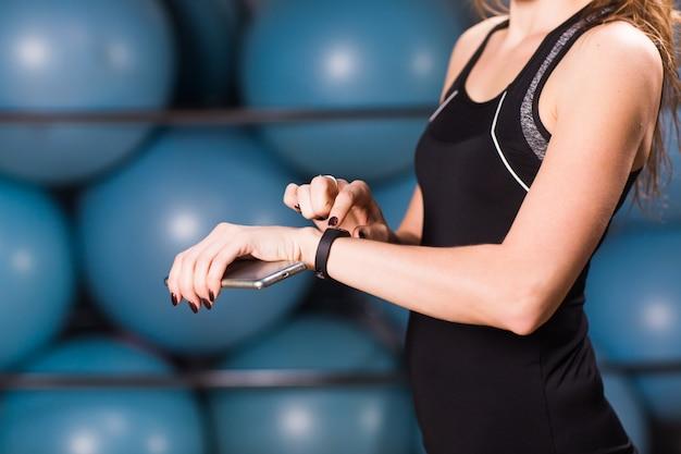 Крупным планом женских рук с фитнес-трекер и смартфон в тренажерном зале