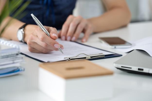 女性の手のクローズアップ。彼女のオフィスに座って何かを書いている女性