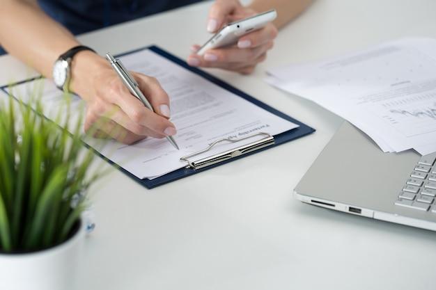 女性の手のクローズアップ。何かを書いて、彼女のオフィスに座っている携帯電話の画面を見ている女性