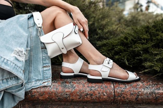 야외에서 흰색 세련된 핸드백을 들고 세련된 가죽 샌들을 신고 여성 다리를 클로즈업합니다.