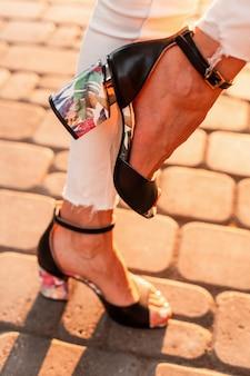 화창한 날 도시의 돌길에서 세련된 청바지를 입은 가죽 블랙 패션 여름 샌들을 입은 여성 다리 클로즈업