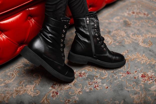 Крупным планом женские ножки в модных джинсах в сезонных стильных кожаных черных ботинках на шнуровке в комнате