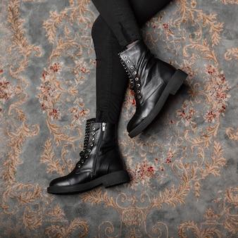 Крупный план женских ножек в винтажных джинсах в стильных брутальных кожаных сапогах на шнуровке