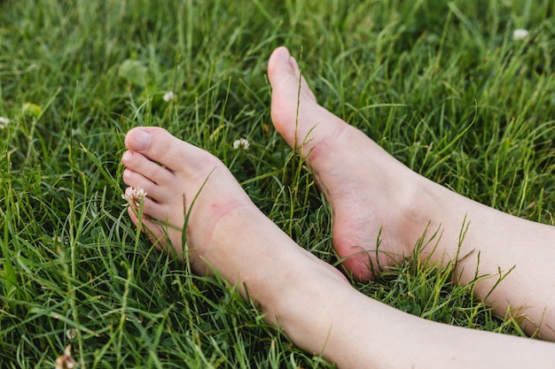 화창한 날 공원에서 잔디에 누워 여성 다리 닫습니다