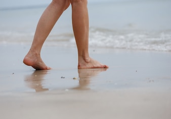 Close up of female legs walking on beach