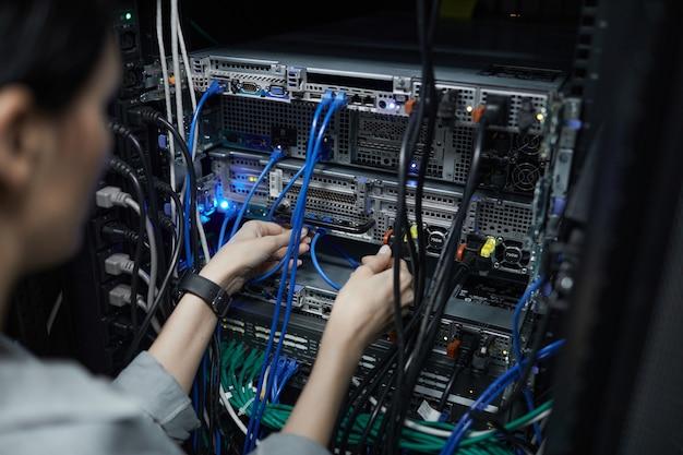 Крупным планом женский сетевой техник, соединяющий кабели в серверном шкафу при настройке суперкомпьютера в центре обработки данных, скопируйте пространство