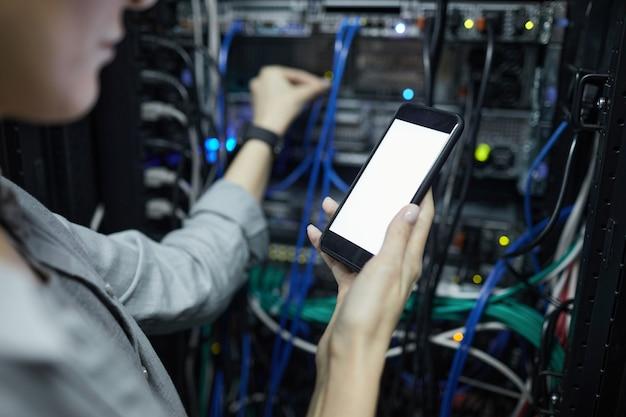 Крупным планом женский сетевой техник, держащий смартфон с пустым экраном при подключении кабелей в серверном шкафу, копирование пространства
