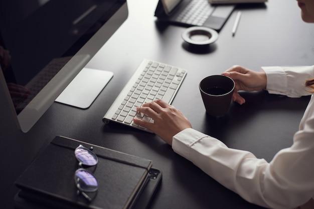 Закройте вверх женского офисного работника, набрав на клавиатуре на столе офиса.