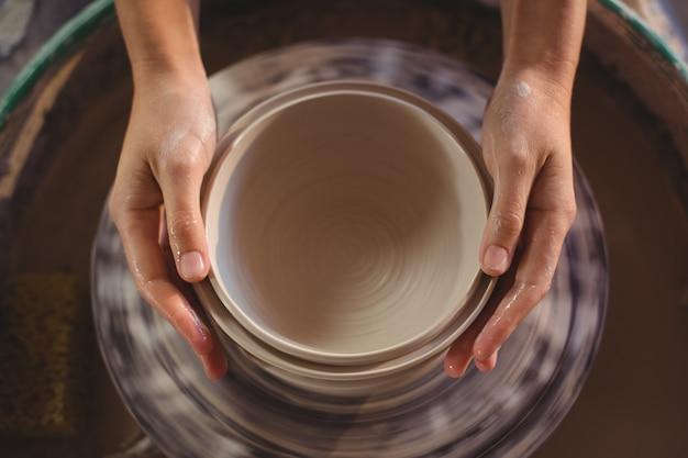 ポットを作る女性の陶芸家のクローズアップ