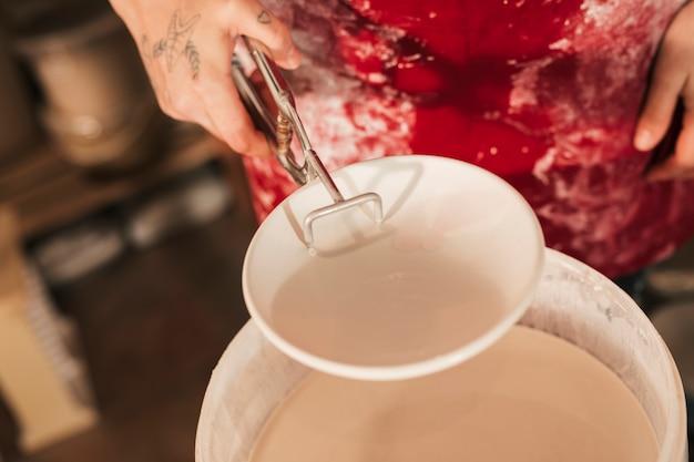 トングで塗られたセラミックプレートを持っている女性の陶工の手のクローズアップ